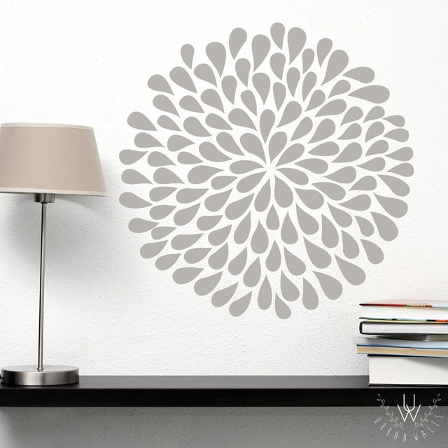 Large grey vinyl flower placed on a white wall above a black bookshelf with a small lamp on it.