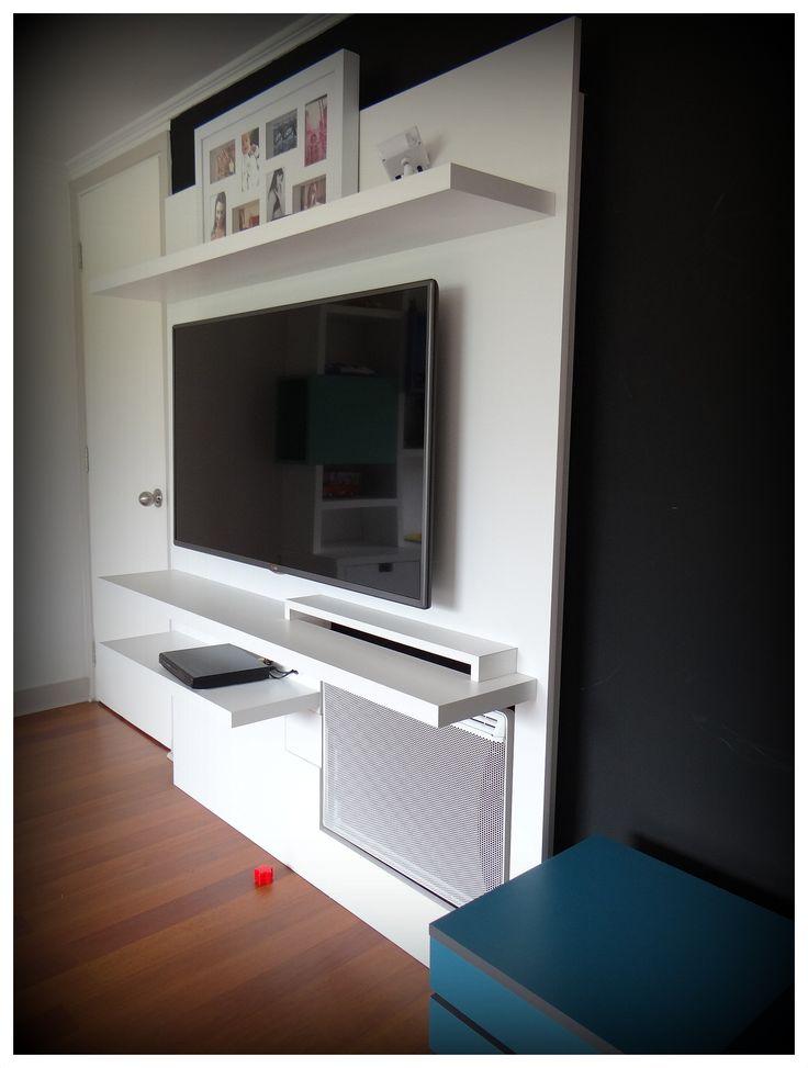 Panel de TV enchapado en lamitech blanco, con inclusión de parrilla de calefacción. Tres voladizos de soporte y dos cubos en treillage en duotono para guardado de objetos.