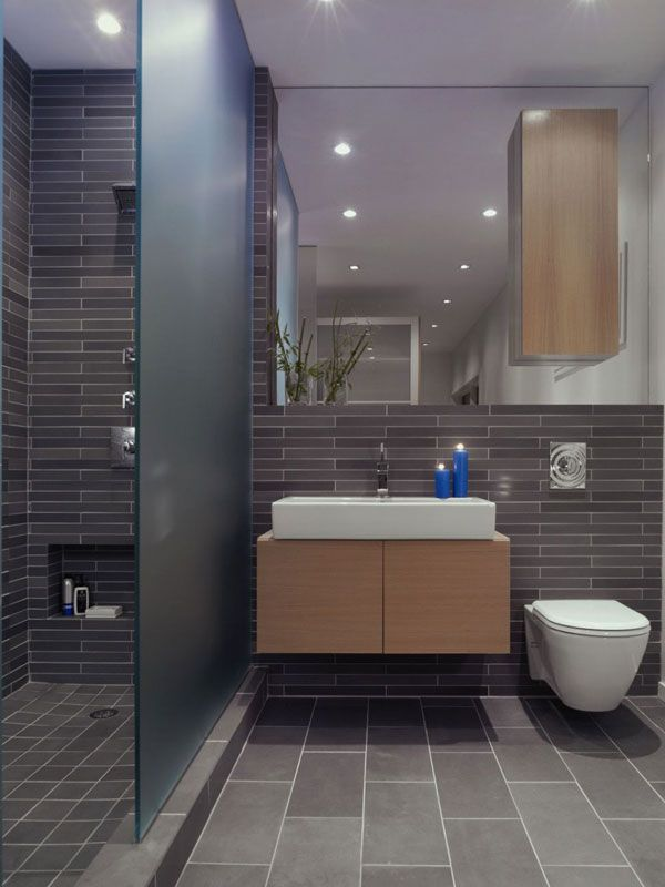 gray tile, diff sizes. tankless toilet. cabinet floating on mirror.