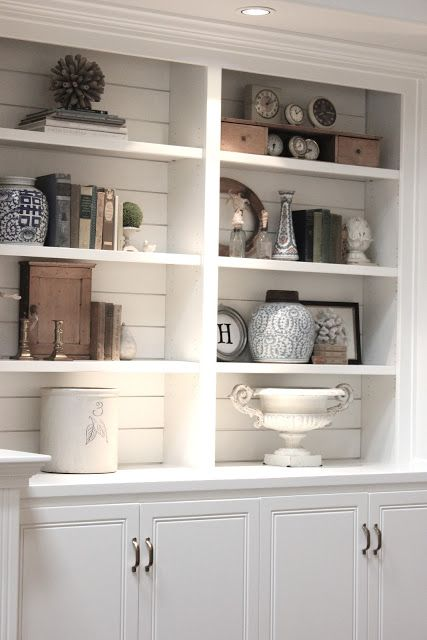 Shiplap planks painted white add texture and architectural interest to these book/collectible shelves.   Via forevercottage.blogspot.com