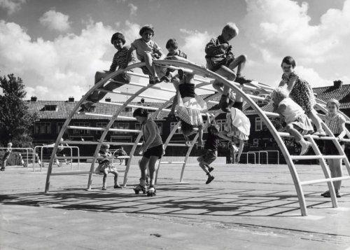 Kinderen spelen op en onder een klimrek, op een speelplaats, Nederland 1963-1975.