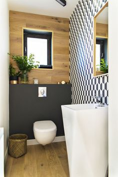 Petite salle de bains déco avec bois, peinture foncée et mur de mosaïque graphique en noir & blanc.