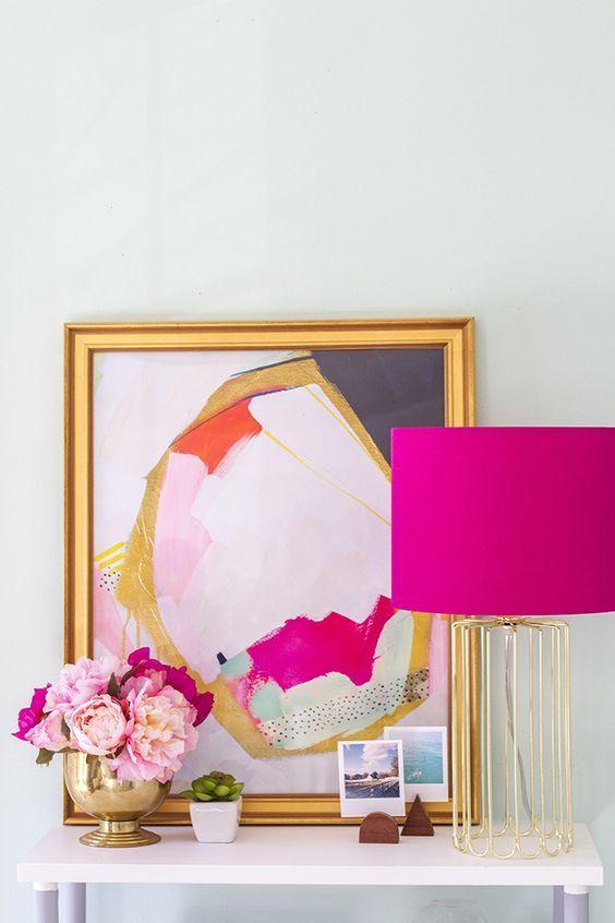 Para as fâs do rosa, vai uma inspiração de decor ultra feminina: aparador com objetos rosa e dourado. Luminária fuchsia com base dourada, quadro e flores.