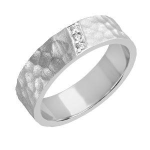 Sandbergin Johka-sormuksen kimaltava timanttinauha käsintyöstetyn Rakka-pinnan keskellä on kuin pieni tunturipuro, joka on matkallaan kohti maailman suuria vesiä raivannut väylänsä läpi loputtoman kivierämaan. Tästä tulee nimi Johka. Kuvassa on 6 mm leveä, flakkaprofiilinen E-260w-Johka, jossa 3 timantin yhteispaino on 0,035ct. Eri leveyksien ja runkoprofiilien ansiosta Johka sopii yhtä hyvin naiselle ja miehelle. Sandberg.fi/