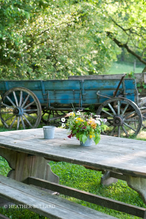 In LOVE!  love this large old blue wagon in the yard...  and the simple table to gather at <3