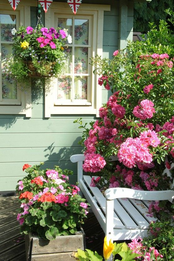 Oh, I LOVE this...the color of the house, the design of the trim, the bunting, hanging basket and the ROSES!: Beautiful Flower, Rose, Cottages Style, Cottages Gardens, Window, House Color, Front Porches, Hanging Baskets, Gardens Benches