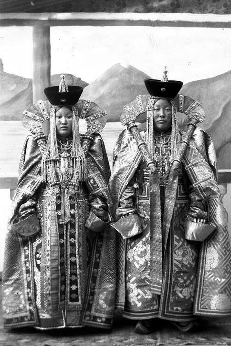 ''Mongol noble women. Early 20th century.'' As incapacitated as Elizabeth I in her farthingaled splendour, these elite women signal their high status by wearing extended sleeves.By obscuring their hands the ladies show that they don't need to use them. Excessive overdressing in this fashion is a strange business. Rather than enjoying the ease wealth should bring them the wearers must suffer any number of exhausting inconveniences.