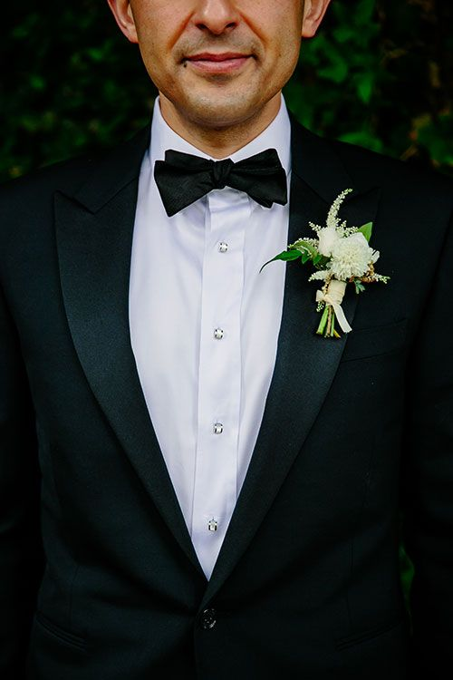 Romantic Flower-Filled Wedding in Austin, Texas, Groom in Navy Suit with White Boutonniere | Brides.com