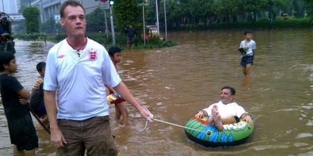 Dua Bule Kegirangan di Tengah Banjir - /via KOMPAS.com