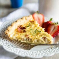 A square photo of a slice of lightly browned Quiche Lorraine, topped with a fresh sprig of thyme, and served with three strawberry halves on a white plate. The photo is from the side of the slice, and visible are the pieces of crisp bacon. There is a fork on the plate and it is on a white wood background with a white linen napkin. A blue terracotta pot is visible in the background.