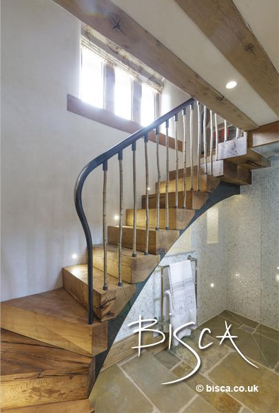 """Rustic oak staircase in 17th Century Barn Conversion. Slabs of green oak are """"stacked"""" to create an authentic feel to this staircase."""