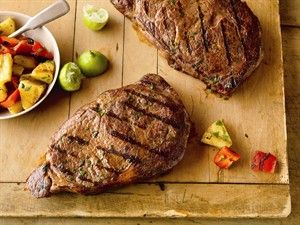 Ribeye steaks are spiced up with cilantro, cumin and ground red pepper and served with a simple salad of pineapple, red pepper and lime.