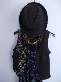 Chaleco de jean con flores bordadas en hilo, collar tejido al crochet.