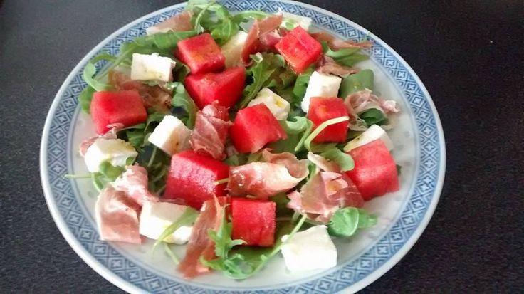Rucola salade met watermeloen, feta en Spaanse ham (kan natuurlijk ook met bijv. serranoham of parmaham).  De dressing is heel simpel: 1 tl honing 1 tl mosterd 1 el extra vierge olijfolie zout - peper