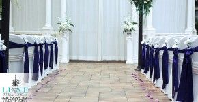 Purple and white wedding ceremony decor, ceremony aisle decor, chair sashes along aisle, chair sashes with flowers, aisle rose petals, pedestals with floral arragements