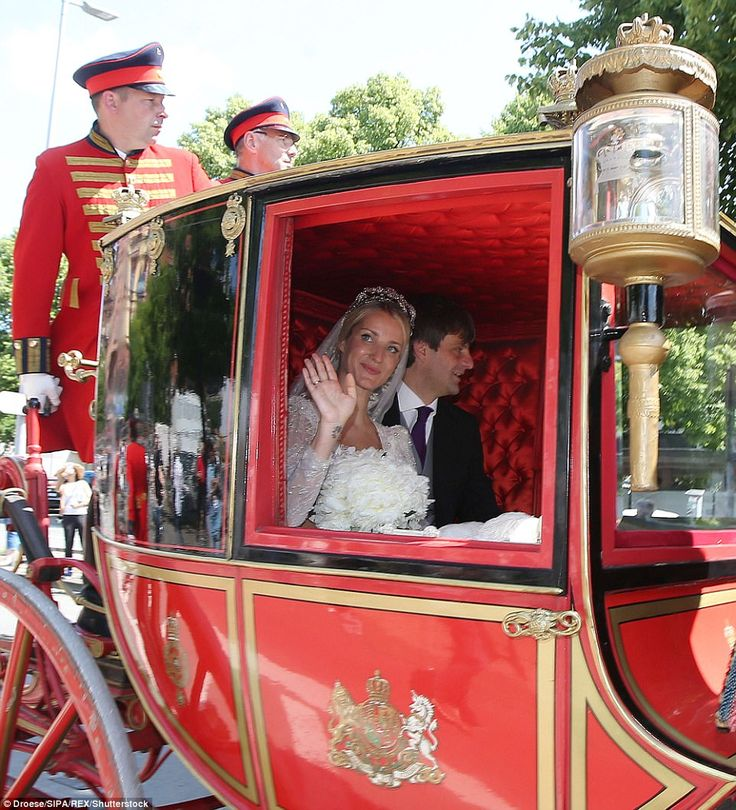 Ekaterina waves to the cheering crowd as the newly-weds drive through the city in a horse-drawn carriage