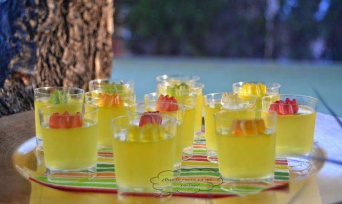 un paquete de gelatina de limón (vienen dos sobres) vasitos de plástico de tipo chupito (3 cm de alto por 2 de ancho) gominolas de ositos para decorar (también se pueden poner pedacitos de limón o lima etc..) 300 ml de agua mineral por cada sobre de gelatina 100 ml de vodka para cada sobre de gelatina