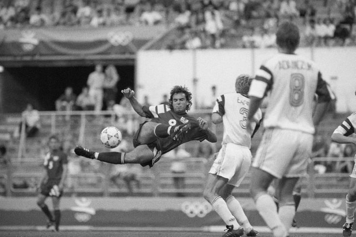 Stephan Leonard Snow of the U.S. soccer team, left, shoots the ball in the preliminary round match of the Olympic tournament vs. Poland, Wednesday, July 29, 1992, Zaragosa, Spain. (AP Photo)