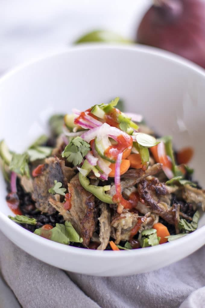 Slow Cooker Pulled Pork Banh Mi Bowls put a healthy twist on the classic Vietnamese sandwich; with pork shoulder, an Asian marinade, pickled veggies + rice.