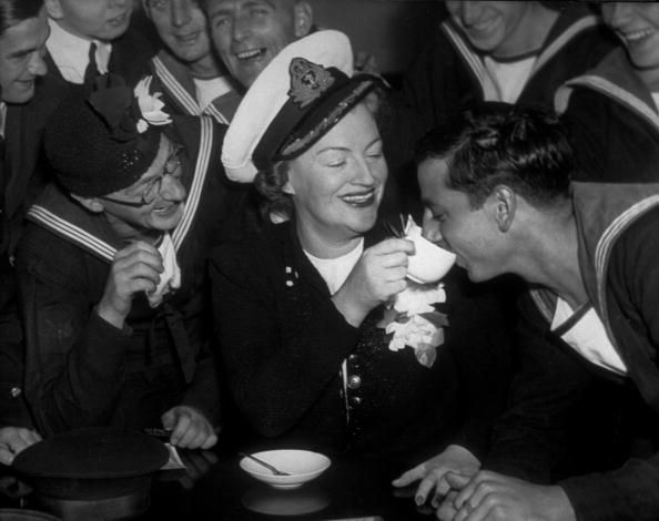 1941: Gracie Fields, with members of the crew of the British warship HMS Manchester. (Photo by Keystone/Getty Images)