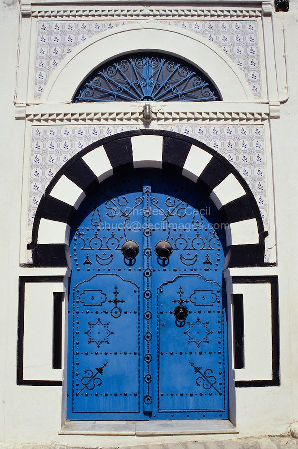 Tunisia, Sidi Bou Said. Traditional Decorated Blue Door and Arch, Entry to a Private Home. The high door knockers date from the time when guests arrived on horseback. COPYRIGHT:© Charles O. Cecil