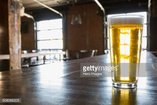 Photo : Pint of beer on counter in empty pub