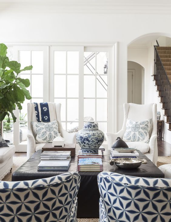 White walls, white slips, blue Peter Dunham pillows, blue patterned upholstered chairs, fig tree, simple staircase, blue and white pottery, woven jute rug