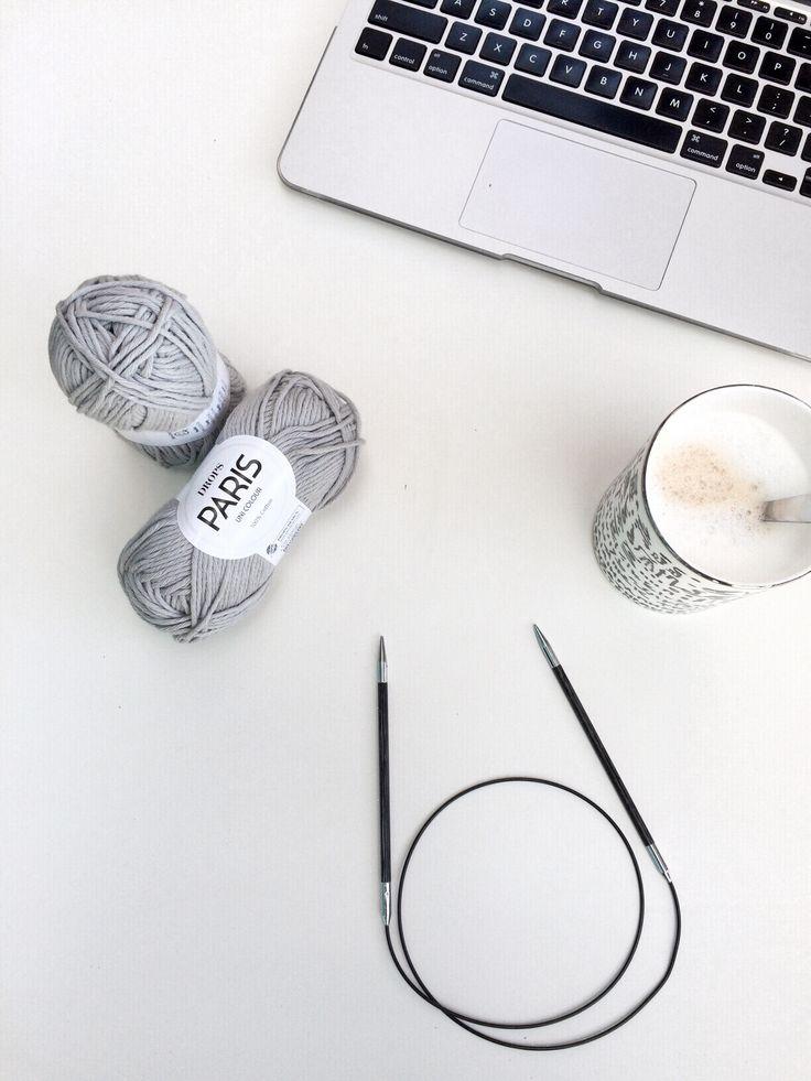 knitting supplies: yarn, circular needles, coffee, and a laptop