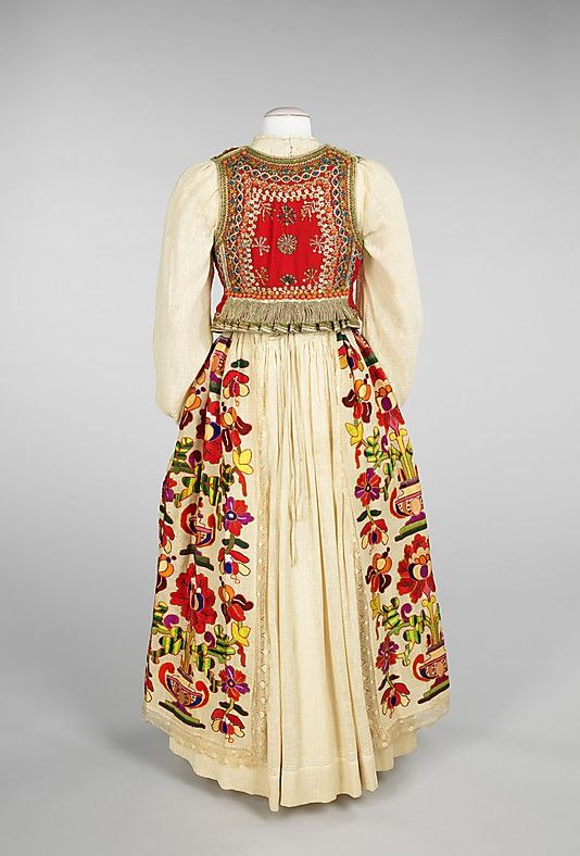 An example of traditional costume that was still being produced in the 20th century, this overskirt displays brilliant color and bold design. The embroidery nearly covers the surface of the skirt and combines both stylistic and naturalistic elements in the depiction of realistic irises and oversized potted flowers with their bold, definitive urns