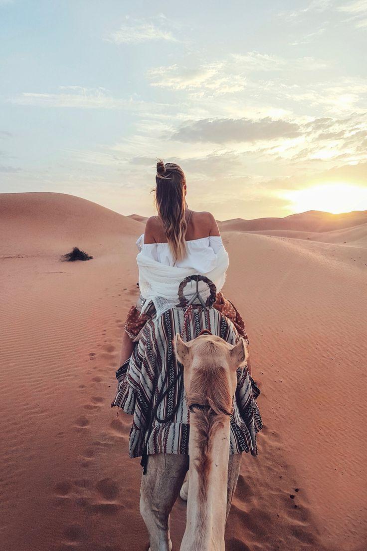 Dieses Foto ist ein Mädchen, das auf einem Kamel …