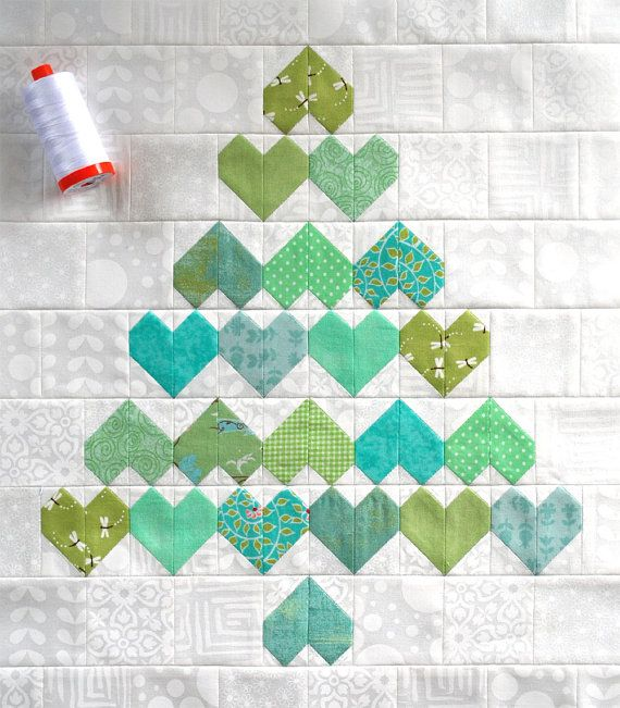 Christmas Hearts Mini Quilt. A Christmas tree quilt that truly shows your love of the holiday, this striking quilt design featuring hearts, zigzags and diamonds is a great pattern for showcasing your favourite Christmas fabrics.