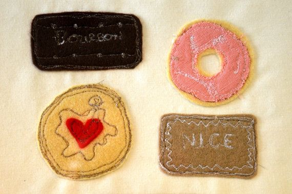 image is 10x8 inches. Four iconic British biscuits- Bourbon cream, Party ring, Nice and Jammie Dodger turned into a freehand embroidered fabric artwork. An ideal gift for any tea and biscuit fan!  Felt is the main fabric used in this image, and detail is added using freehand machine embroidery, a method of drawing with a sewing machine.  Underneath the image the word time for tea are hand stamped onto linen. All items are promptly posted using Royal mails first class, signed for service.