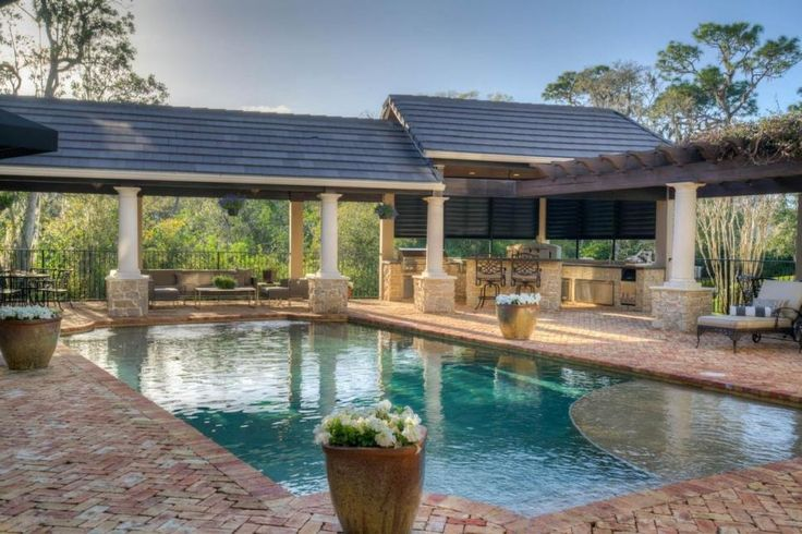 Perfectly manicured gardens flank the walkway leading to this Odessa, Florida, home's front door. The brick walkways weave their way through lush green grass and around another garden in front of the garage. Outdoor living areas, including a swimming pool and gourmet kitchen, make it easy to entertain in such beautiful surroundings. >> http://www.hgtv.com/design/ultimate-house-hunt/2017-ultimate-house-hunt/curb-appeal/curb-appeal-sculpted-gardens-luxury-home