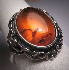 Victorian Amber Ring -- This beautiful amber ring holds a natural piece of Baltic amber at its center surrounded by sterling silver with a lovely rich patina. The amber measures about 10 x 15mm oval. There are European silver hallmarks on the outside of the silver shank. Overall the ring measures about 3/4 inch long by about 3/4 inch wide from side to side.