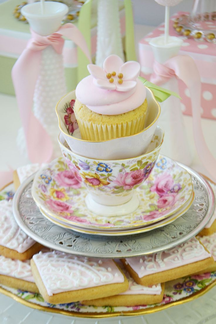 Lovely lace cookies and china teacups holding flower cupcakes are a sweet part of a vintage dessert table. By Bake Sale Toronto
