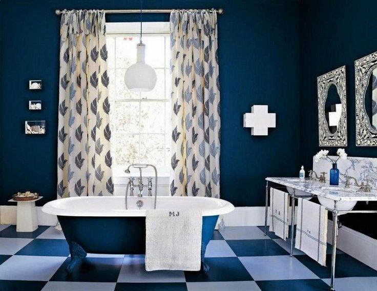 salle de bain colorée avec une peinture murale bleu roi, carrelage de sol en damier noir/blanc et une baignoire îlot en blanc et bleu roi