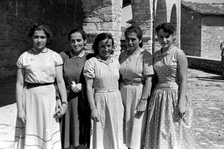 San Giorgio di Cascia, fine anni '50.  Alcune giovani donne del paese con il vestito buono della festa vicino ai possenti archi del porticato della chiesa del paese. La società rurale sta cambiando in meglio, anche per le donne.
