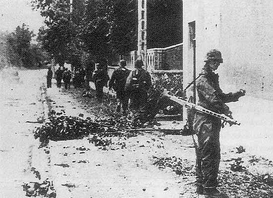 SS-Schütze Günther Streelow looks at the camera while III.Zug of SS-Aufklärungs Kompanie 15 walks through the streets of Rots, after fierce fighting against the Canadian 2nd Armoured Brigade in Norrey-en-Bessin, Normandy. 9 June 1944.