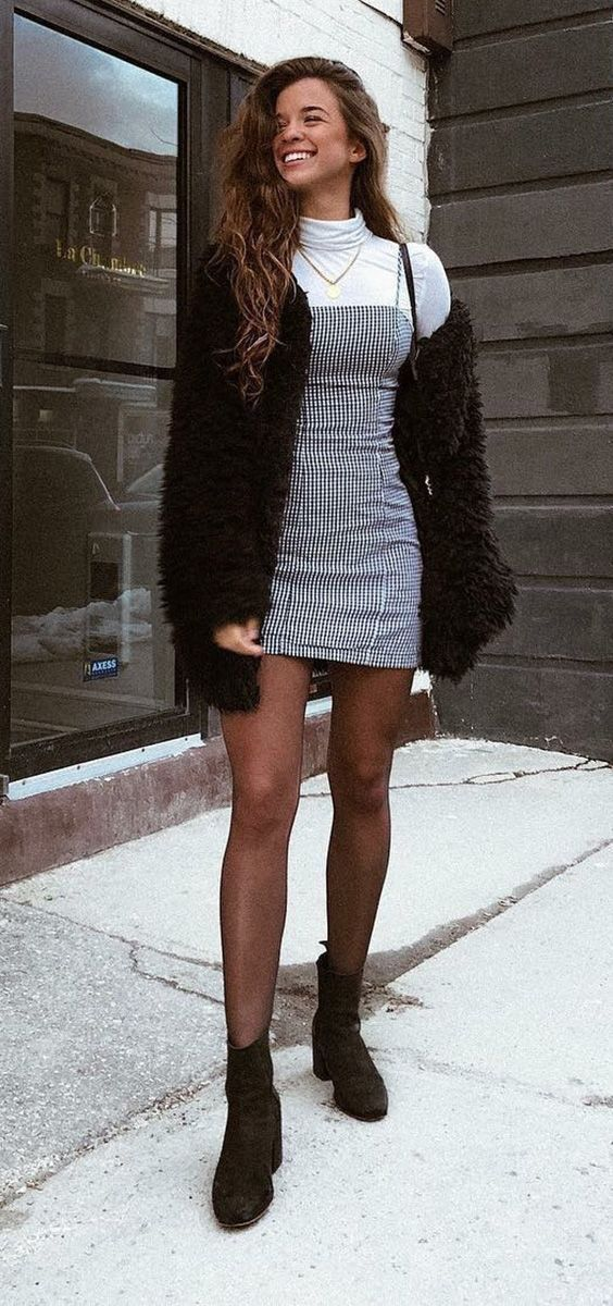 White turtle neck, gray dress, and black tights an…