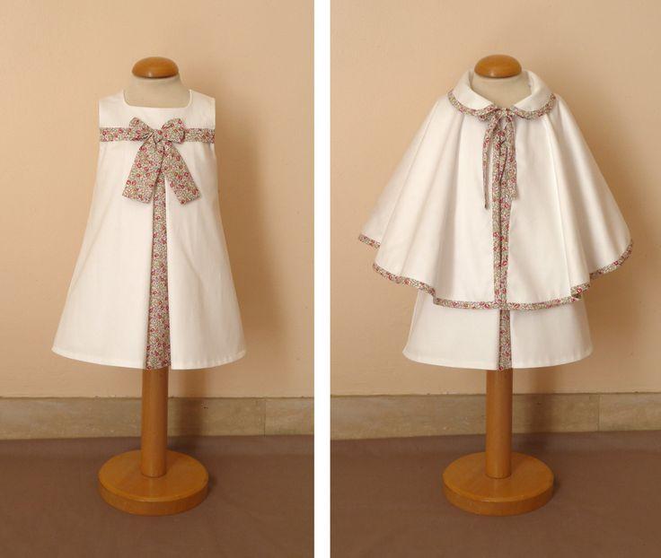 Pour une petite fille de 12 mois, une robe Suzanne en satin de coton blanc et liberty Eloïse rose doublée de voile de coton associée à une petite cape en satin de coton doublée polaire à col claudine et bordée de biais. la cape se ferme par une nouette;...