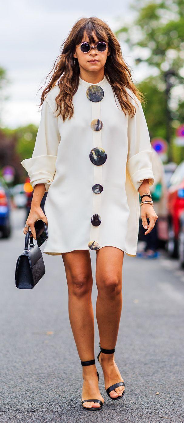 Une robe courte blanche avec de gros boutons au milieu, des escarpins ouverts noirs, un petit sac noir et de petites longues rondes.