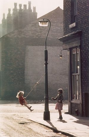 Photograph by Shirley Baker. Two young girls swing on a rope attached to a lampost outside a corner shop in Hulme, Manchester in the evening light, 1965.