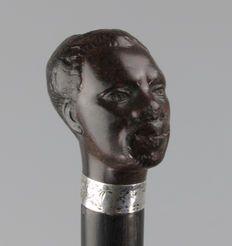 """Ebben houten wandelstok met een """"Bois Durci"""" Afrikaanse mannen kop - 19e eeuw."""