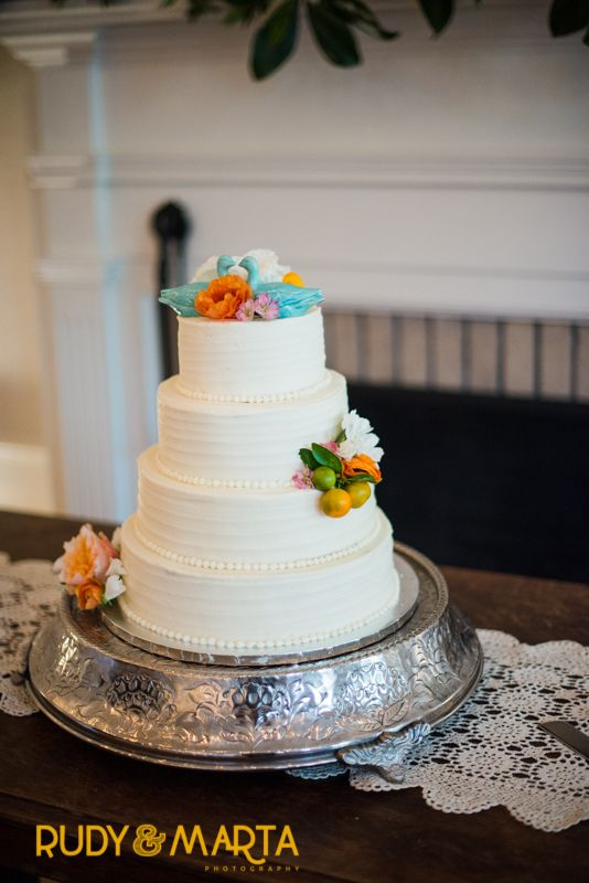 simple and elegant wedding cake is adorned with orange ranunculus, pink larkspur, peach roses, white scabiosa and fresh calamondins.