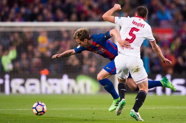 Ivan Rakitic of FC Barcelona is brought down by Clement Lenglet of Sevilla FC during the La Liga match between FC Barcelona and Sevilla FC at Camp Nou stadium on April 5, 2017 in Barcelona, Catalonia.