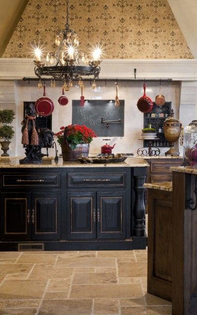 French Country kitchen with a distressed black kitchen island and rustic wood cabinets  (via Rick Hoge)