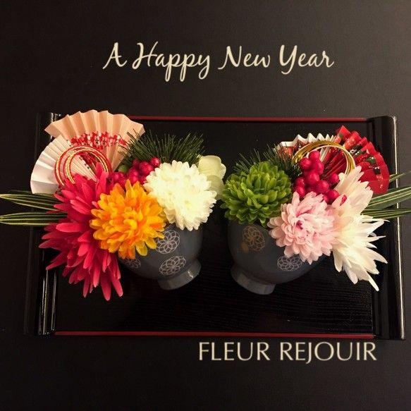 ご覧いただき、ありがとうございます。アーティフィシャルフラワー(造花)のお正月飾りです。2個セットでお盆も付いております!お正月に是非、いかがでしょうか。玄関、リビングなど、どこに飾ってもとても華やかです。テーブルやカウンターにポンと置いていただくだけで、お正月の雰囲気になります♪色とりどりのマムたち。その他、松などお正月らしいアレンジを可愛らしいお碗の中に収めました!左・・・ピンクのマム(菊)にイ%E