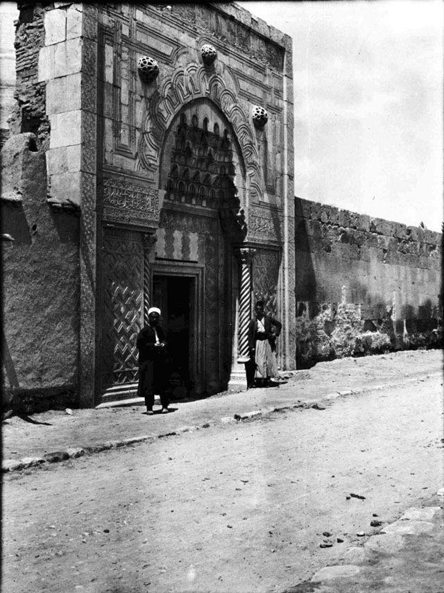 Konya Buyuk Karatay Medrese, doorway - example of Islamic art, combining Arabic striped stonework, Greek Corinthian columns and Koranic script with Seljuk architecture and interlacing geometric patterns in the decoration. Fattuh and another man standing outside. Date taken: May 1905	 Photographer: Gertrude Bell Location: Konya - Turkey. Subject date: 1256
