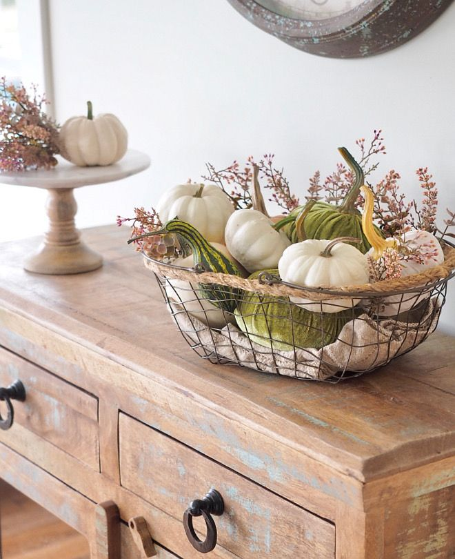 Metal basket with faux white pumpkins and velvet pumpkins, squash and greenery. Farmhouse Fall decor #fall #falldecor #farmhousefall #farmhousefalldec…
