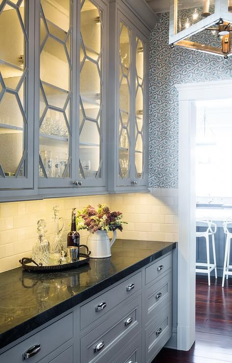 lined with shelves over gray drawers adorned with polished nickel cup pulls paired with a black granite countertop and a white subway tiled backsplash